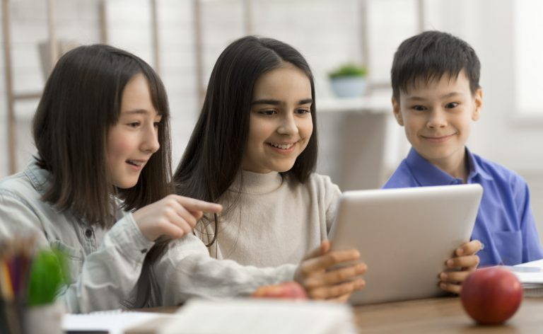 Children watching videos on digital tablet in class