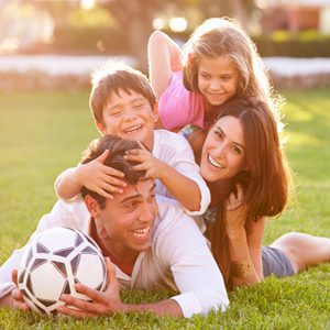 Family Lying In Pile Up On Grass Together